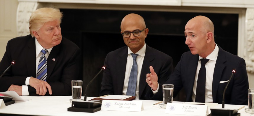 In this June 19, 2017, file photo President Donald Trump, left, and Satya Nadella, Chief Executive Officer of Microsoft, center, listen as Jeff Bezos, Chief Executive Officer of Amazon, speaks during an American Technology Council roundtable.