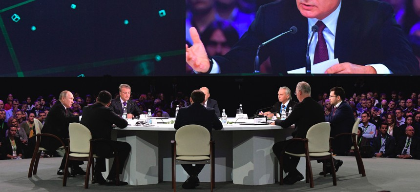 Russian President Vladimir Putin, left, attends a panel discussion at the Artificial Intelligence Journey (AIJ) forum in Moscow, Russia, Saturday, Nov. 9, 2019.