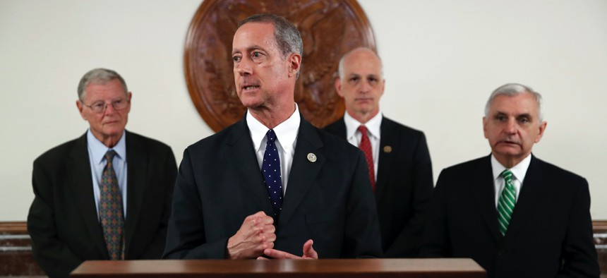 In this 2018 photo, Sen. Jim Inhofe, R-Okla., left, stands as Rep. Mac Thornberry, R-Texas, second from left, speaks, accompanied by Rep. Adam Smith, D-Wash., and Sen. Jack Reed, D-R.I.