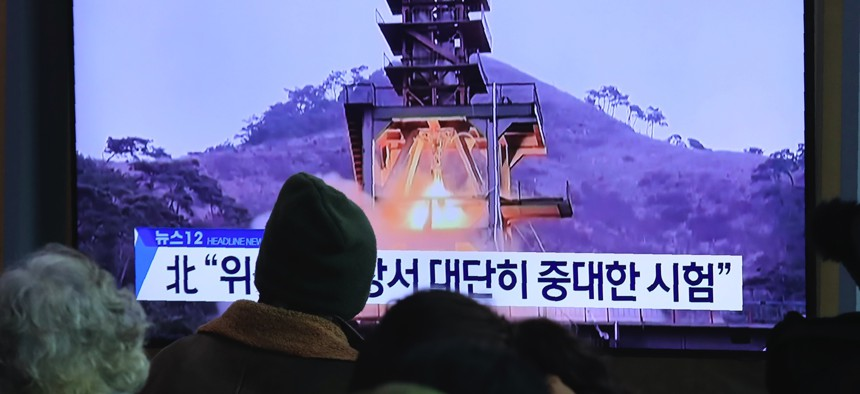 """People watch a TV screen at the Seoul Railway Station in Seoul, South Korea, on Dec. 9, 2019. North Korea said Sunday it carried out a """"very important test"""" at its long-range rocket launch site. The sign reads: """"Very important test."""""""