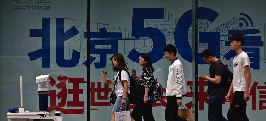 People walk toward a police robot mounted with surveillance cameras patrol past a 5G network advertisement at a shopping district in Beijing, Wednesday, May 15, 2019.