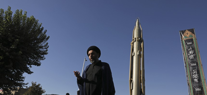 A Muslim cleric walksin downtown Tehran, where a Shahab-3 surface-to-surface missile is on display on Sept. 25, 2019.