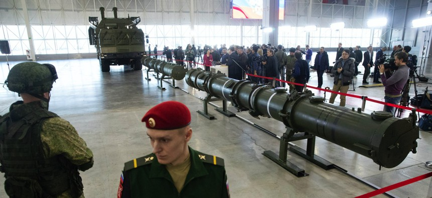 Russian military officers stand by as the 9M729, center, its launcher, left, and the 9M728, right, land-based cruise missiles are displayed in Kubinka outside Moscow, Russia.