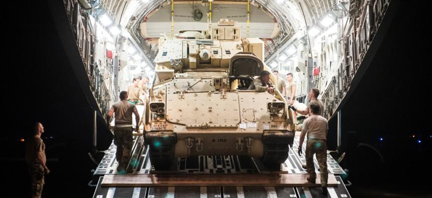 An M2 Bradley Fighting Vehicle is loaded onto a U.S. Air Force C-17 Globemaster III at Ali Al Salem Air Base, Kuwait, Oct. 30, 2019.