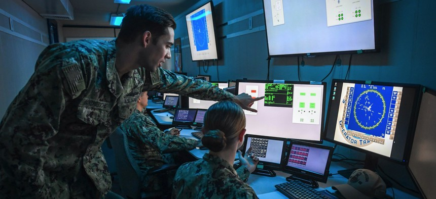 Lt. Aaron Van Driessche, a warfare tactics instructor in San Diego, pilots the U.S. Navy's virtual combat curriculum aboard USS Paul Hamilton inside the On Demand Trainer, a new portable simulator.