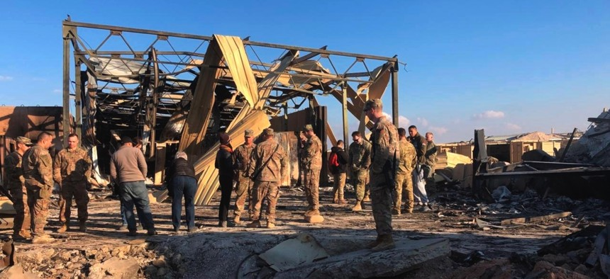 U.S. soldiers stand at a site of Iranian bombing at Ain al-Asad air base in Anbar, Iraq, Monday, Jan. 13, 2020.