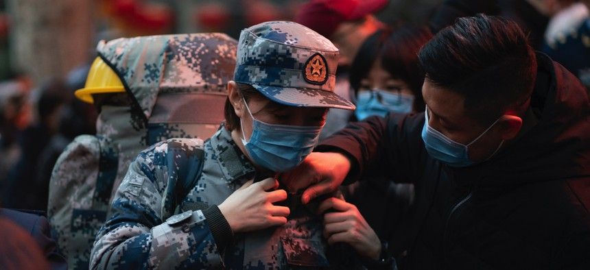In this photo taken January 24, 2020 and released by Xinhua News Agency, a military medic from the Air Force Medical University prepares to leave for Wuhan from Xi'an, capital of northwestern China's Shaanxi Province.