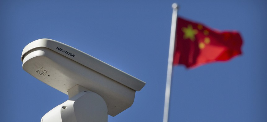 A Chinese flag flies near a Hikvision security camera monitoring a traffic intersection in Beijing, Tuesday, Oct. 8, 2019