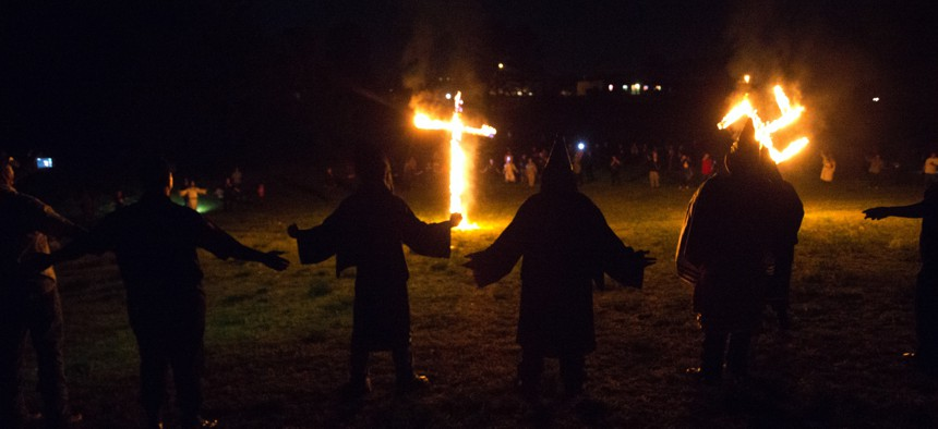 """In this Saturday, April 23, 2016 photo, members of the Ku Klux Klan participate in cross and swastika burnings after a """"white pride"""" rally in rural Paulding County near Cedar Town, Ga."""