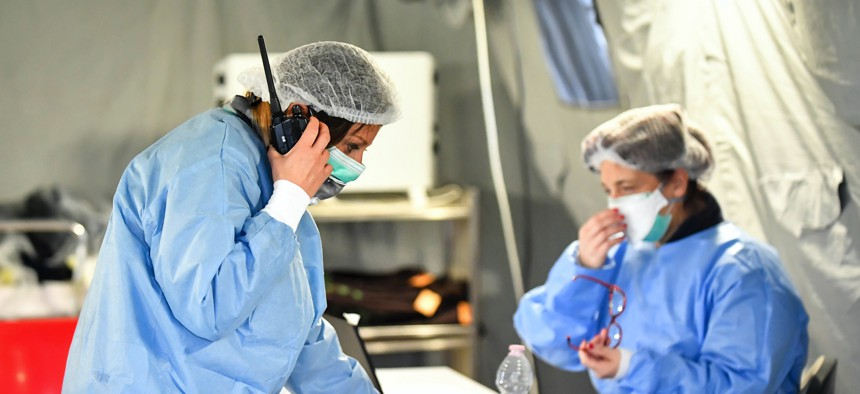 In this Saturday, Feb. 29, 2020, photo, paramedics work in a tent that was set up outside the hospital of Cremona, northern Italy.
