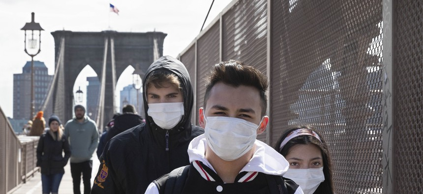 People wear masks as they cross the Brooklyn Bridge, Monday, March 16, 2020 in New York.