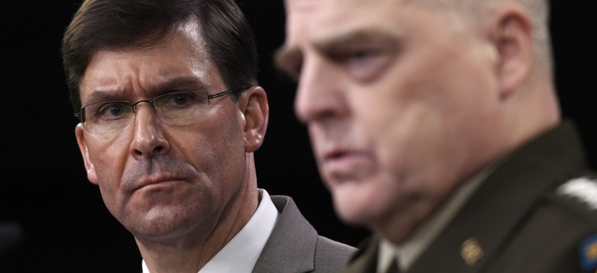 Defense Secretary Mark Esper, left, listens as Chairman of the Joint Chiefs of Staff Army Gen. Mark Milley, right, speaks during a briefing at the Pentagon in Washington, Monday, March 2, 2020.