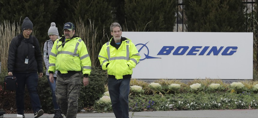 Workers walk past a Boeing Co. sign as they leave the factory where the company's 737 Max airplanes are built, Tuesday, Dec. 17, 2019, in Renton, Wash.