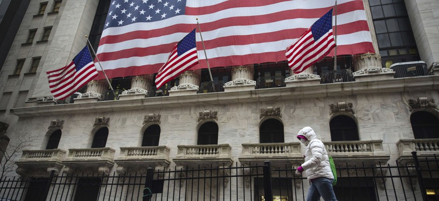 A pedestrian wearing a surgical mask and gloves walks past the New York Stock Exchange on Thursday, March 19, 2020, in New York.