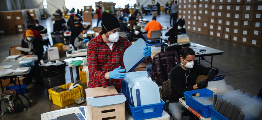 Workers wearing personal protective equipment builds splash guards during a mass manufacturing operation to supply New York City government with protection to distribute against COVID-19, Friday, March 27, 2020, at the Brooklyn Navy Yard in New York.