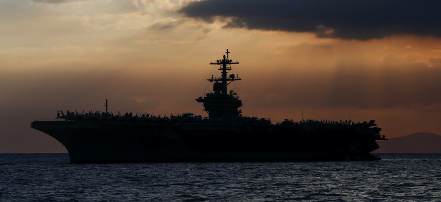 In this April 13, 2018, file photo the USS Theodore Roosevelt aircraft carrier is anchored off Manila Bay west of Manila, Philippines