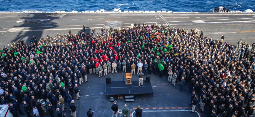 In this Dec. 15, 2019, photo, Capt. Brett Crozier, commanding officer of the aircraft carrier USS Theodore Roosevelt (CVN 71), addresses the crew during an all hands call on the ship's flight deck while training in the eastern Pacific Ocean.