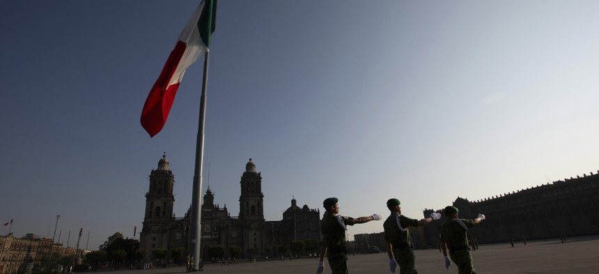 Mexican soldiers leave the Zocalo square after deploying the national flag in Mexico City, Sunday, March 22, 2020.