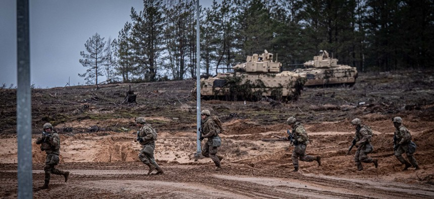 Soldiers from the U.S. Army's 1st Cavalry Division charge across a road during a live-fire exercise at Pabradė Training Grounds in Lithuania, Feb. 12, 2020. More than 500 were deployed in 2019 to reinforce NATO's presence there.