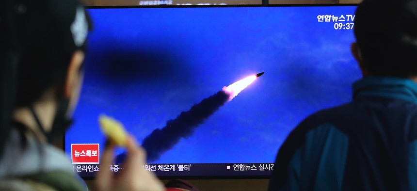 People watches a televsion screen showing a file image of North Korea's missile launch during a news program at the Seoul Railway Station in Seoul, South Korea, Saturday, March 21, 2020.