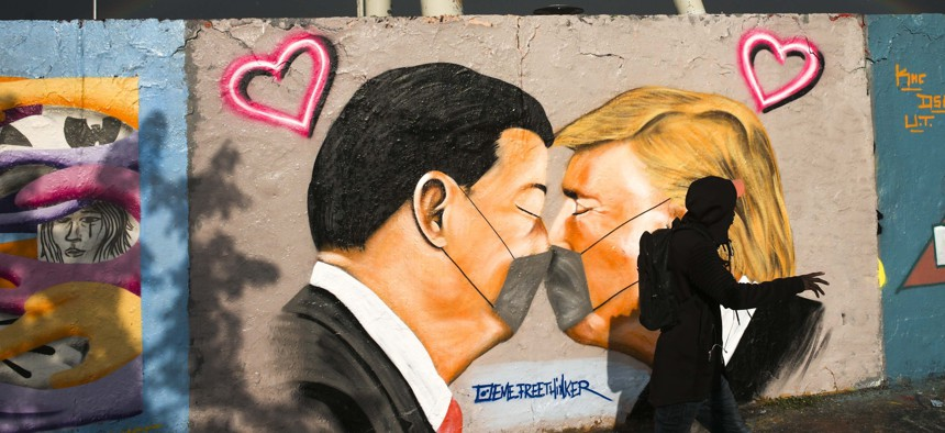 A man walks in front of graffiti depicting US President Trump, right, and China's President Xi Jinping kissing each other with face masks, displayed at a wall in the public park Mauerpark in Berlin, Germany, Wednesday, April 29, 2020.