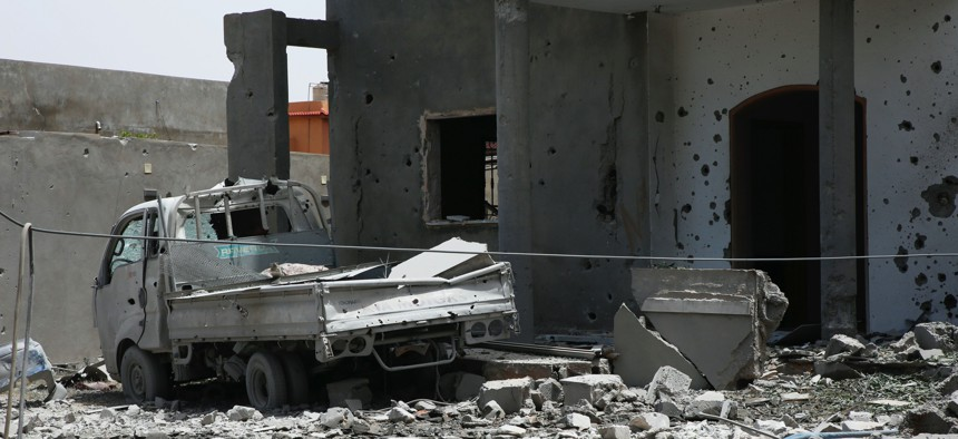 In this June 15, 2019, file photo, a vehicle and structure is damaged from fighting in the region of Tajoura, east of the Libyan capital Tripoli.