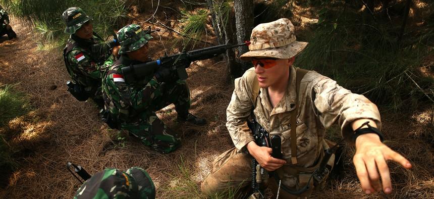 U.S. Marine Cpl. Joseph Josleyn talks with troops of Indonesia's Korps Marinir during Rim of the Pacific (RIMPAC) Exercise 2014.