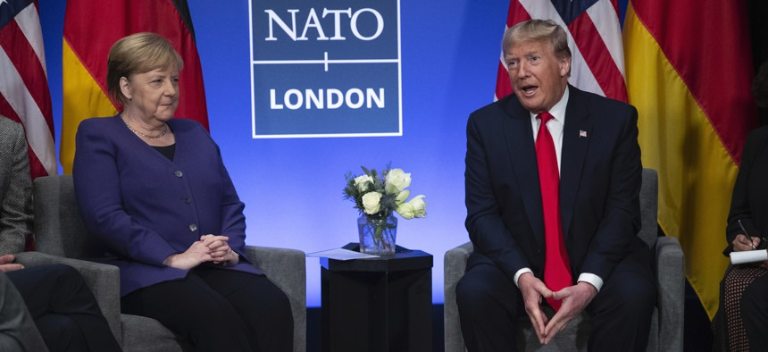 """President Donald Trump speaks during a meeting with German Chancellor Angela Merkel during the NATO summit at The Grove, Wednesday, Dec. 4, 2019, in Watford, England. President Donald Trump is calling Canadian Prime Minister Justin Trudeau """"two-faced"""" aft"""