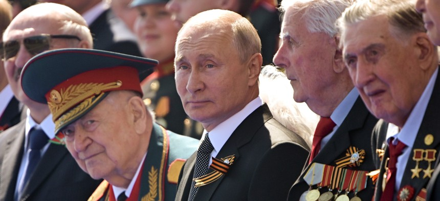 In this file photo taken on Wednesday, June 24, 2020, Russian President Vladimir Putin, center, watches the Victory Day military parade marking the 75th anniversary of the Nazi defeat in Moscow.