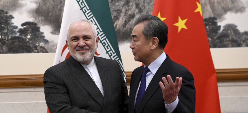 China's Foreign Minister Wang Yi, right, shakes hands with Iran's Foreign Minister Mohammad Javad Zarif during a meeting at the Diaoyutai state guest house in Beijing Tuesday, Dec. 31, 2019.