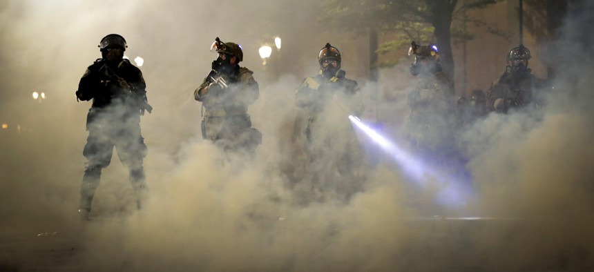 Federal officers are surrounded by smoke as they push back demonstrators during a Black Lives Matter protest at the Mark O. Hatfield United States Courthouse Wednesday, July 29, 2020, in Portland, Ore.