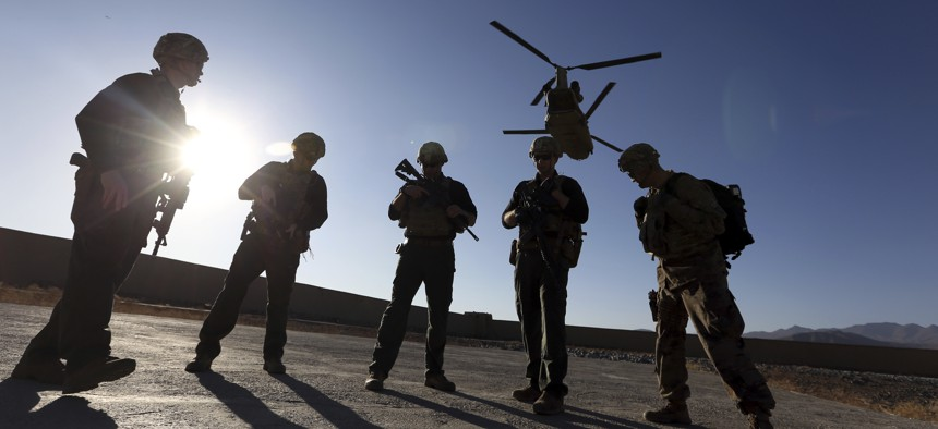 In this Nov. 30, 2017 file photo, American soldiers wait on the tarmac in Logar province, Afghanistan. The U.S. is pausing movement of troops into Afghanistan and quarantining 1,500 new arrivals to country due to virus.