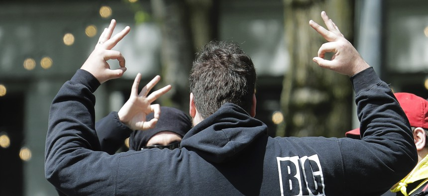 """People standing with a a group of protesters wearing shirts with the logo of the far-right Proud Boys group flash hand signs that are known to signify """"White Power"""" during a small protest against Washington state's stay-at-home orders, Friday, May 1, 2020"""