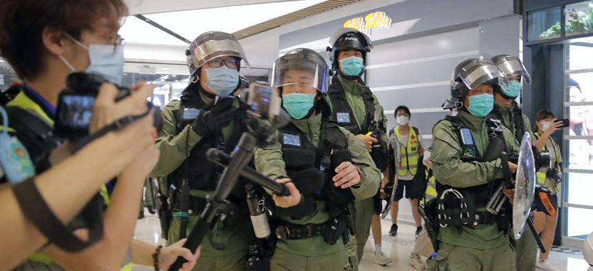 A riot police officer uses baton to hit a journalist's microphone during a protest to mark one-year anniversary of the Yuen Long subway attack, at a shopping mall in Hong Kong, Tuesday, July 21, 2020.