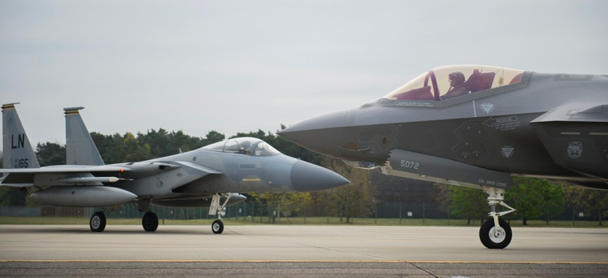 An F-35A Lightning II from the 34th Fighter Squadron at Hill Air Force Base, and an F-15C Eagle from the 493rd Fighter Squadron, stand by to take-off for a training sortie at Royal Air Force Lakenheath, England.