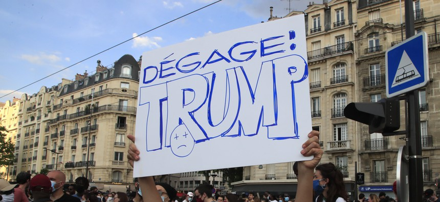 """A protester holds a poster reading """"Trump go away"""" during a demonstration Tuesday, June 2, 2020 in Paris."""