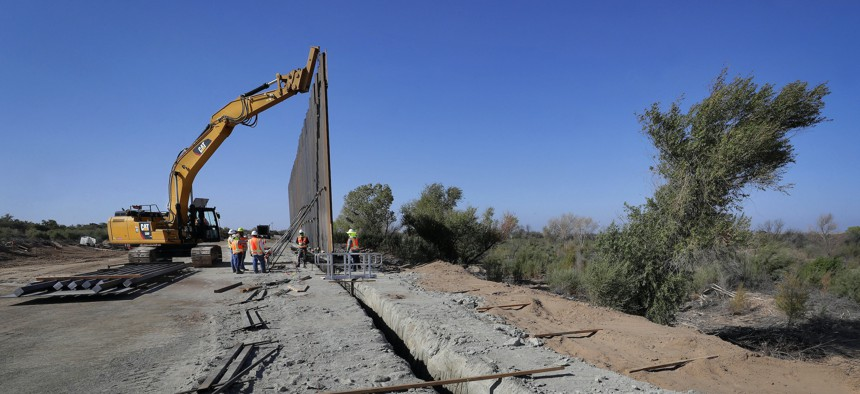 Government contractors erect a section of Pentagon-funded border wall along the Colorado River, in Yuma, Ariz., in November 2019.