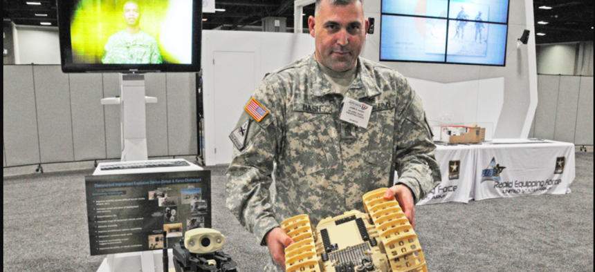 Sgt. Maj. James Hash shows a Rapid Equipping Force-procured Dragon Runner, operated by Soldiers remotely in Afghanistan for reconnaissance and counter improvised explosive device operations. The venue is the Washington Auto Show, in February 2013.