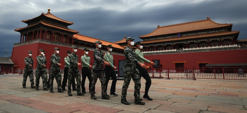 Chinese People's Liberation Army soldiers march past the closed Forbidden City in Beijing on May 25, 2020.