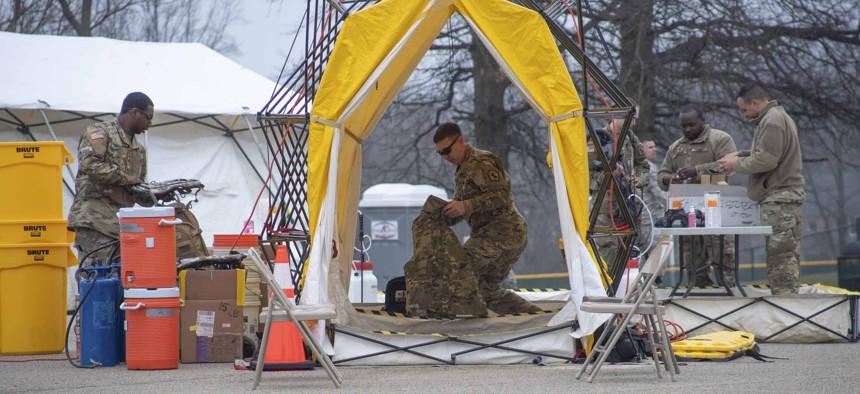 Pennsylvania Air National Guardsmen set up gear at a mass coronavirus test center in Upper Dublin Township, Pa., March 20, 2020.
