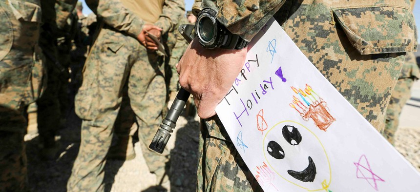 A Marine in Afghanistan holds a holiday card received from a grade school in Maryland, Dec. 22, 2018.