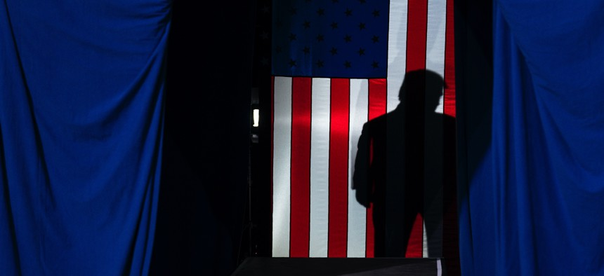 The shadow of President Donald Trump falls on a flag Feb. 20, 2020, in Colorado Springs, Colo.