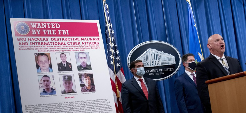 A poster showing six wanted Russian military intelligence officers is displayed at a news conference at the Department of Justice on Oct. 19, 2020, in Washington.