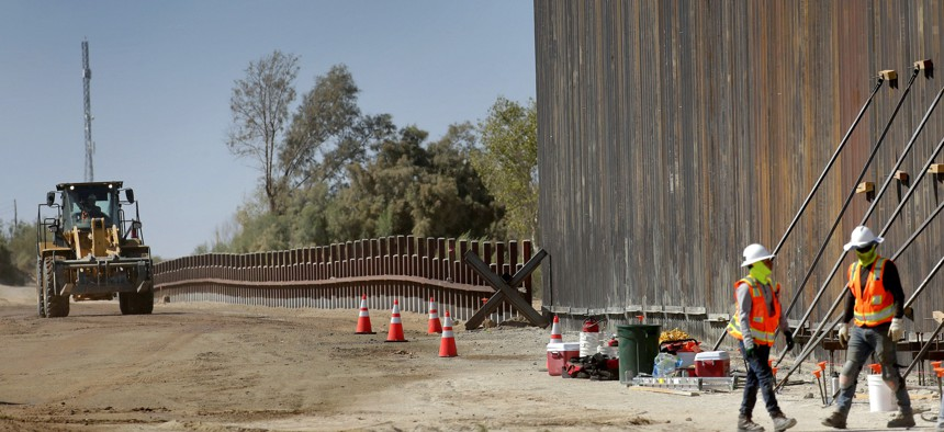 In this Sept. 10, 2019, file photo, government contractors erect a section of Pentagon-funded border wall along the Colorado River, in Yuma, Ariz.