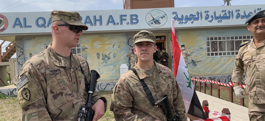 U.S. soldiers stand guard during the hand over ceremony of Qayyarah Airfield, Iraqi Security Forces, in the south of Mosul, Iraq early Friday, March 27, 2020.