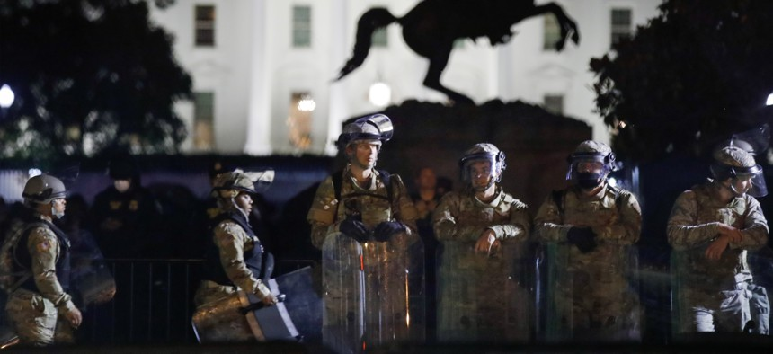 A line of DC National Guard members stand in Lafayette Park as demonstrators gather to protest the death of George Floyd, Tuesday, June 2, 2020, near the White House in Washington. Floyd died after being restrained by Minneapolis police officers.