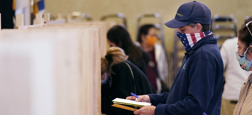 Bruce Lowell looks down at his ballot as he enters a voting booth at an early voting location, Tuesday, Oct. 27, 2020, in Lowell, Mass.