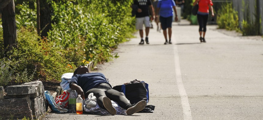 A homeless person lies down along the Hudson River Park walkway in New York City as people pass her by.