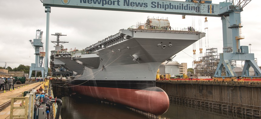 Workers flood the dry dock holding the aircraft carrier John F. Kennedy.