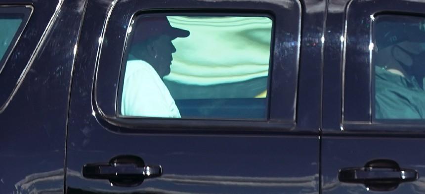 President Donald Trump rides in a motorcade vehicle as he departs Trump International Golf Club, Sunday, Dec. 27, 2020, in West Palm Beach, Fla.